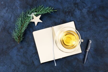 New Year resolutions, flatlay overhead shot with copy space, on a dark blue background with a Christmas decoration and a cup of tea