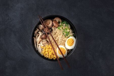 Ramen. Soba noodles with eggs, shiitake mushrooms, and vegetables, shot from the top on a black background with chopsticks and a place for text 写真素材