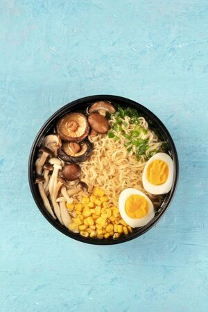 Ramen. Soba noodles with boiled eggs, shiitake mushrooms, and vegetables, shot from the top on a blue background with a place for text 写真素材