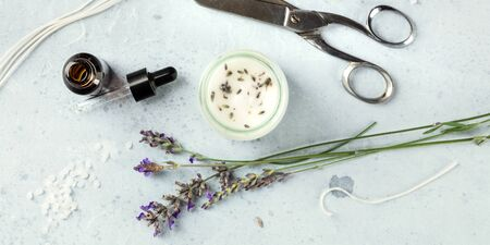 Handmade lavender scented candle with essential oil, flowers, wax, wicks, and scissors, overhead panoramic flat lay shot. An artisanal Christmas gift in a recycled glass jar
