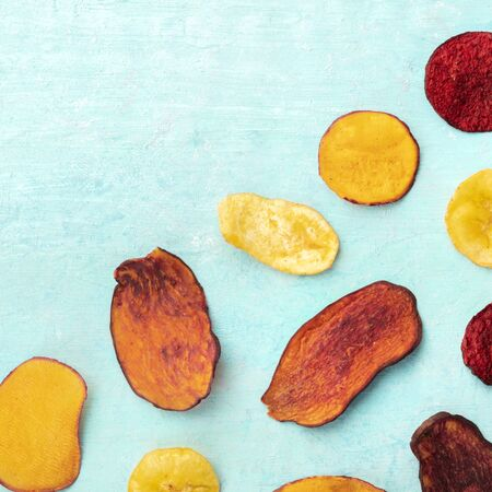 Dried fruit and vegetable chips, square overhead shot with copyspace. Healthy vegan snack, an organic food flatlay pattern on a blue background
