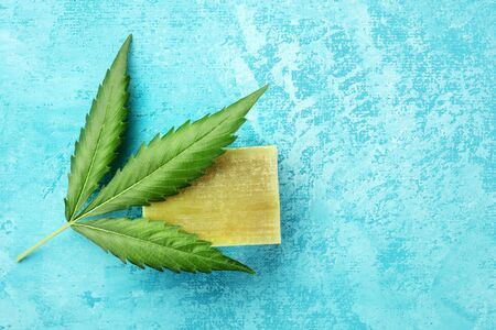 A cannabis leaf with homemade hemp soap bar, shot from the top on a turquoise blue background with copy space