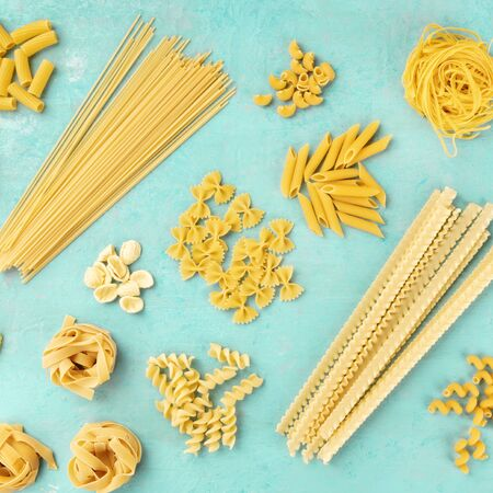 Italian pasta, square overhead shot, a flat lay on a blue background. Spaghetti, penne, farfalle, macaroni and others