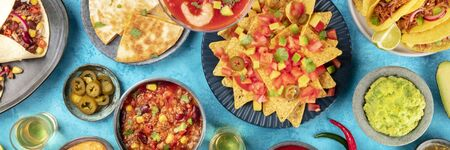 Mexican food, panoramic overhead shot. Dishes like nachos, quesadillas, chili con carne, burrito wraps, with guacamole, jalapenos and tequila, a flatlay