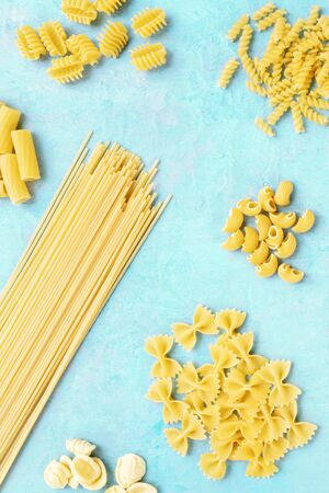 Dry pasta variety, flatlay banner, overhead shot on a blue background