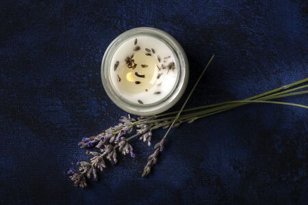 A burning lavender scented candle, shot from the top on a dark background with a place for text. Zero waste Christmas, a handmade New Year gift in a recycled glass jar 写真素材