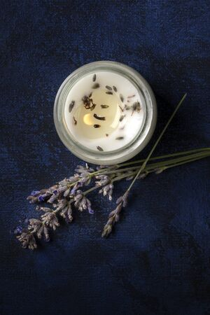A burning lavender scented candle, shot from above on a dark background with copyspace. Zero waste Christmas concept, a handmade New Year gift in a recycled glass jar