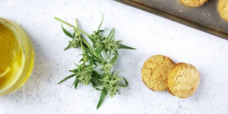 A panorama of cannabis butter cookies with marijuana buds and cannaoil, homemade healthy biscuits, overhead shot