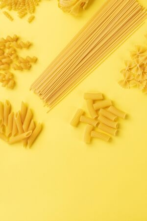 Italian pasta, shot from the top on a yellow background with copyspace, a flat lay banner
