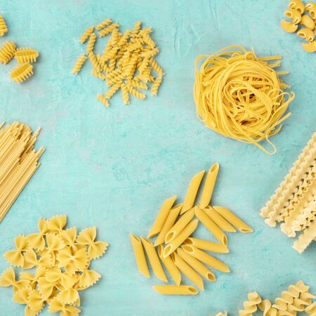 Italian pasta variety, square overhead flat lay shot on a teal blue background, a frame with copyspace