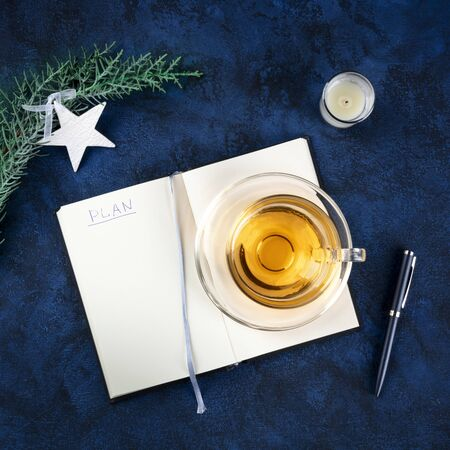 New Years resolutions or bucket list concept. A square flat lay overhead shot with the word Plan and a place for text, on a dark blue background with a Christmas decoration and a cup of tea