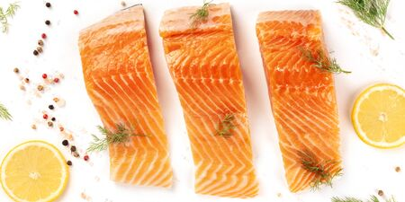 Salmon slices close-up with lemon and dill, overhead shot with salt and pepper on a white background. Cooking fish, a flat lay composition