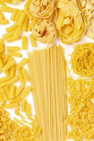 Italian pasta variety, flat lay banner, top shot on a white background. Spaghetti, macaroni, farfalle, fusilli, pappardelle etc 写真素材