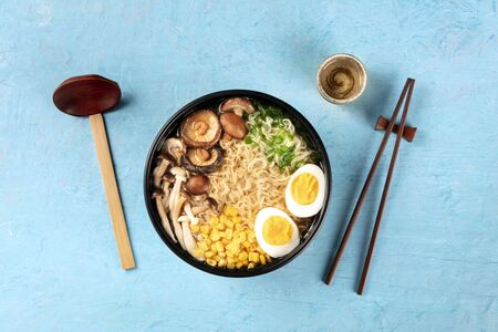 Ramen soup. Soba noodles with eggs, shiitake mushrooms, and vegetables, shot from the top with sake, traditional wooden spoon, and chopsticks 写真素材