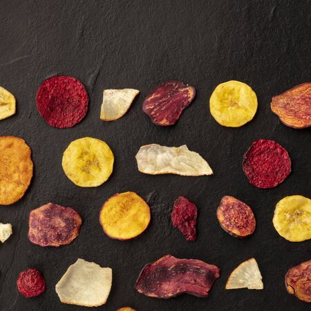 Dried fruit and vegetable chips, square overhead shot with a place for text. Healthy vegan snack, an organic food flat lay pattern on a dark texture