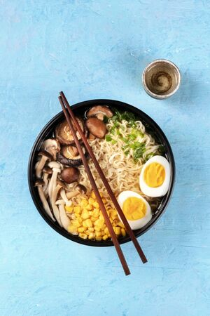 Ramen. Soba noodles with boiled eggs, shiitake mushrooms, and vegetables, overhead shot on a blue background with chopsticks, a cup of sake, and a place for text