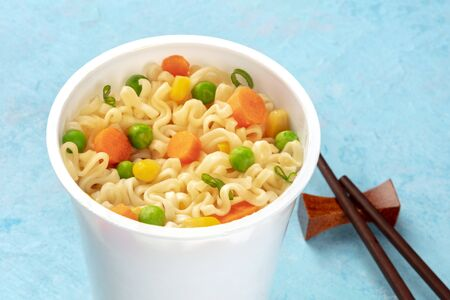 Ramen cup close-up, instant soba noodles in a plastic cup with vegetables, with chopsticks