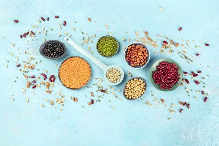 Legumes, shot from above on a blue background with a place for text. Vibrant pulses including colorful beans, lentils, chickpeas, a flat lay composition with copy space 版權商用圖片