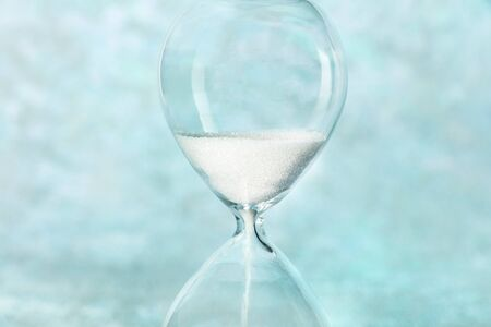 Time is running out concept. A close-up of an hourglass with sand falling through, on a teal blue background with a place for text 版權商用圖片