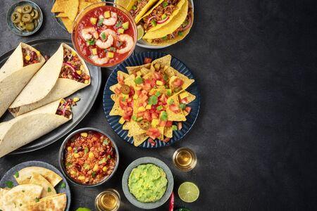 Cibo messicano, molti piatti della cucina messicana, piatto, top shot su sfondo nero con un posto per il testo. Nachos, tequila, guacamole, burritos, chili con carne e copy space