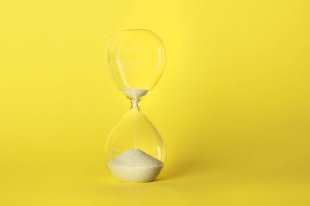 Time is running out concept. An hourglass with sand falling through, on a vibrant yellow background with copy space