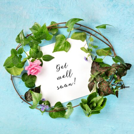Get well soon square card with a wreath of green ivy leaves and a tender pink rose, top shot of a design template