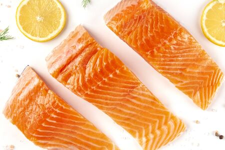 Slices of salmon with lemon, a flat lay close-up top-down shot with salt and pepper, cooking fish, on a white background