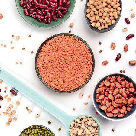 Assortimento di legumi su sfondo bianco. Impulsi, tiro quadrato dall'alto. Fagioli colorati vibranti, lenticchie, ceci, semi di soia, piatti piatti