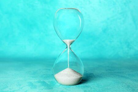El tiempo se está acabando el concepto. Un reloj de arena con arena cayendo, sobre un fondo azul vibrante con un lugar para el texto Foto de archivo
