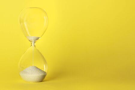 Il tempo sta finendo il concetto. Una clessidra su uno sfondo giallo vivace con un posto per il testo