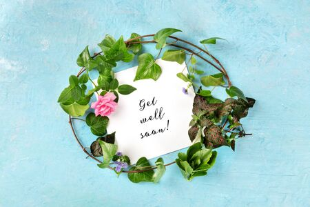 Get well soon card with a wreath of green ivy leaves and a tender pink rose, overhead shot on a blue background Stockfoto