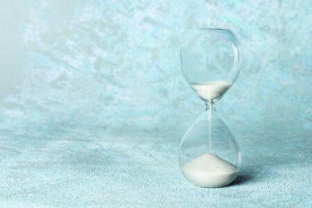 Un reloj de arena sobre un fondo azul claro con un lugar para el texto. Gestión del tiempo o concepto de presión con espacio de copia