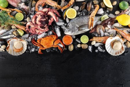 Fish and seafood variety, a flat lay top shot, with copy space on a dark background. Sea bream. shrimps, crab, sardines, squid, mussels, scallops and caviar