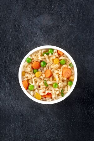 Ramen cup, instant soba noodles in a plastic cup, with green peas and carrot, overhead shot with copy space on a dark background