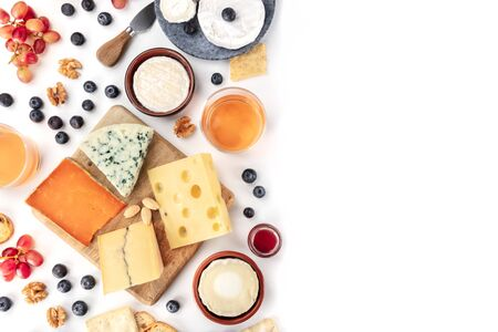 Cheese board background, a flatlay top shot on white with copy space. Blue cheese, red Leicester, Emmental, goat cheese, Brie and others with wine, fruits, nuts and almonds, with a place for text
