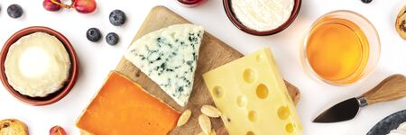 Cheese platter flatlay panorama on a white background. Blue cheese, red, goat cheese, and others, with wine, fruits and almonds Stock fotó - 135940529