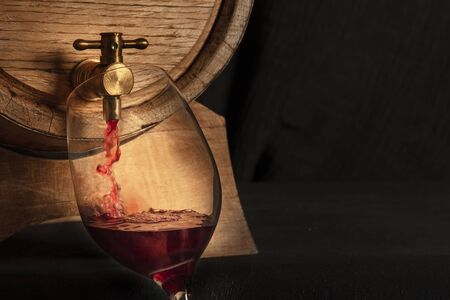 Pouring wine panoramic shot, a design template with copy space. A wine glass filled from an oak barrel, a closeup on a dark background with a place for text