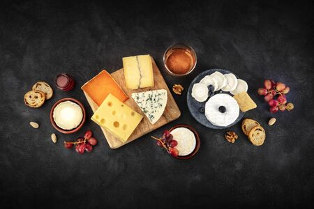 Cheese platter with wine and fruit, a flat lay overhead shot on a black background with copy space