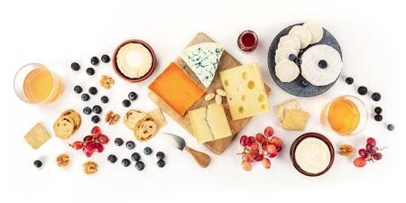 Cheese board, a flat lay panorama on a white background. Blue cheese, red Leicester, Emmental, goat cheese, Brie and others, shot from the top with wine and fruits Stock fotó