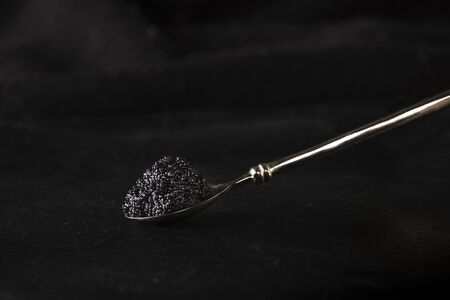 Black caviar on a spoon, on a dark background with copy space. Gourmet food
