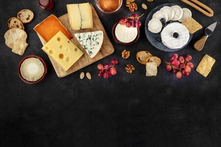 Cheese assortment design template. Blue cheese, soft cheese, wine, grapes, shot from the top on a black background with copy space Фото со стока