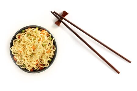 Instant noodles bowl with carrot and scallions, with chopsticks, shot from the top on a white background