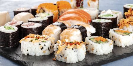 Large sushi set panoramic close-up. An assortment of various maki, nigiri and rolls