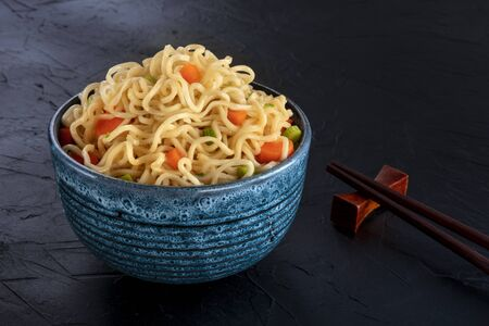 Instant noodles bowl with carrot and scallions, with chopsticks on a black background