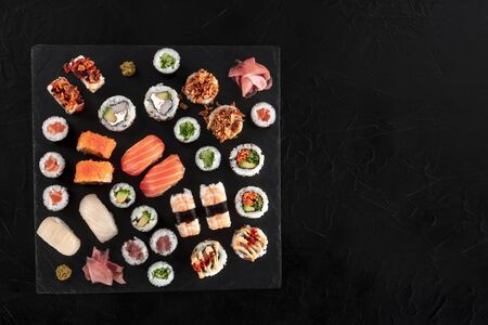 Large sushi set, shot from the top on a black background with a place for text. An assortment of various maki, nigiri and rolls