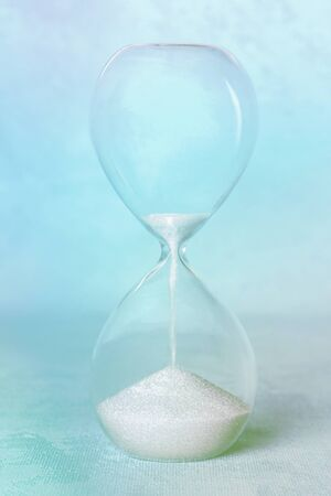 Time concept. An hourglass on an abstract background, with sand leaking through. Blue toned image
