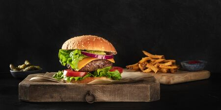 Burger with beef, cheese, onion, tomato, and green salad, a side view panorama on a dark background with French fries and pickles, with copy space