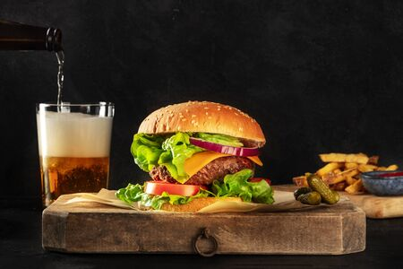 Burger and beer. Hamburger with beef, cheese, onion, tomato, and green salad, a side view on a dark background with copy space, pickles, and French fries. Selective focus