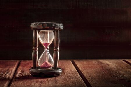 Time is running out concept. An hourglass with sand falling through, on a dark wooden background with copy space Standard-Bild