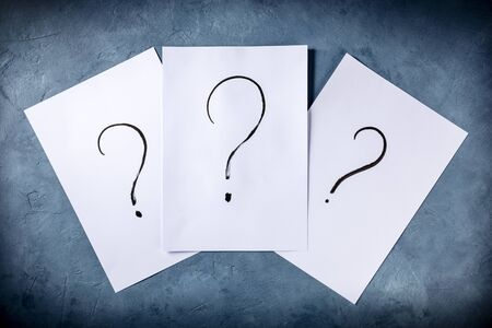 Question marks, written in ink on a piece of standard office paper, shot from the top